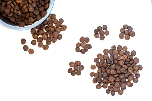 Dry pet food for dogs and cats in a bowl and a little loose, in the shape of a paw on a white background