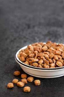 Dry pet food in a white ceramic bowl on black background with copy space
