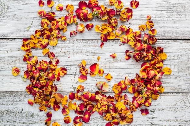 白い木製の壁にバラの花びらを乾燥します。