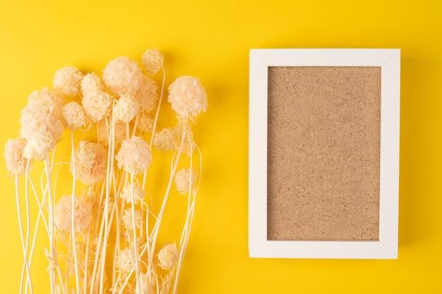 フレームの上のテキストのためのスペースで上から撮影された黄色の表面の乾燥したピンクの花上面図
