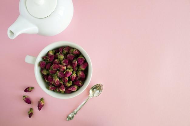 Сухие розовые розы в белой чашке и вид сверху на чайник