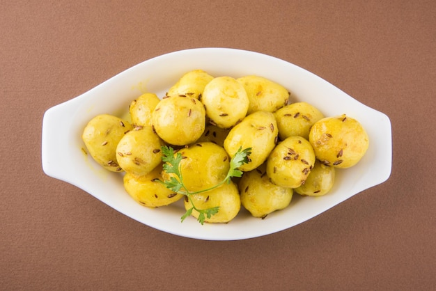 Dry potato sabzi or jeera aloo fry is an indian lunch or dinner recipe served in a plate with roti or paratha