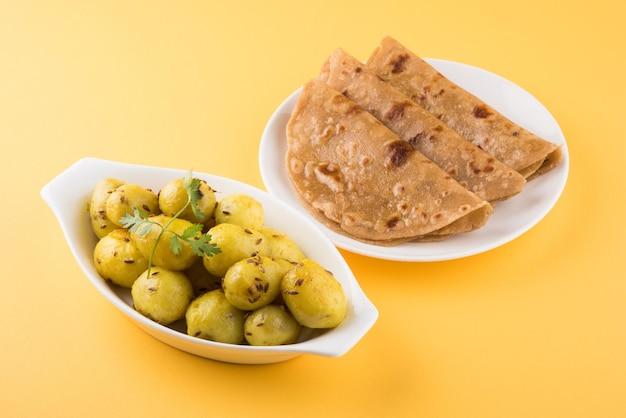 마른 감자 사브지 또는 지라 알루 프라이는 로티 또는 파라타와 함께 접시에 제공되는 인도식 점심 또는 저녁 요리법입니다.