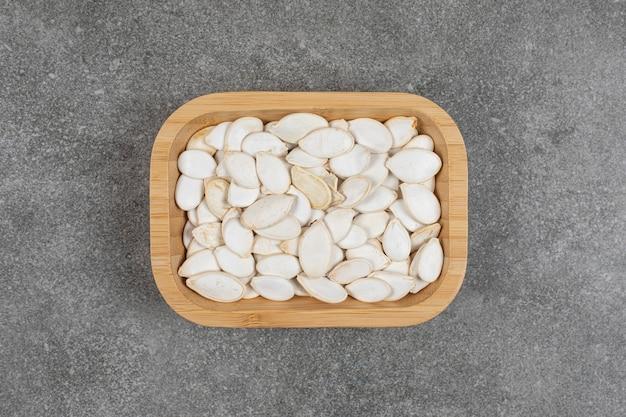 Semi di zucca secchi sul piatto di legno.