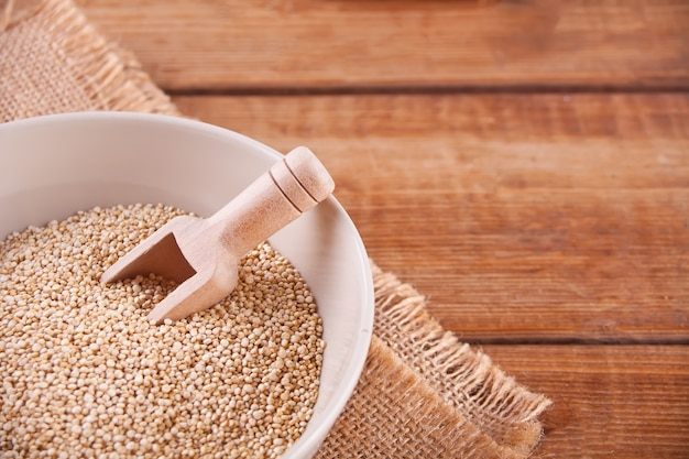Dry quinoa in a bowl on the wooden table.
