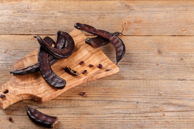 Dry raw carob pods on wooden background