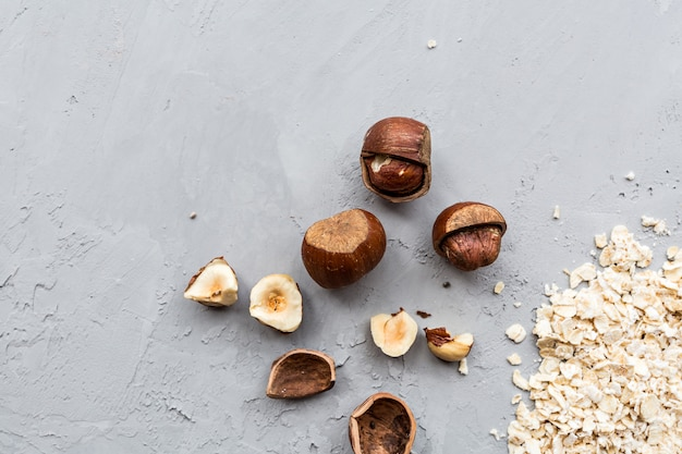 Dry raw oat flakes and hazelnuts lying on gray concrete background.