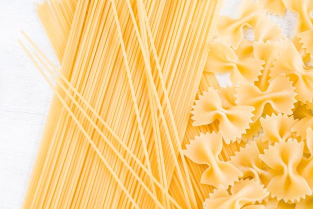 乾燥した生パスタファルファッレと白い背景のスパゲッティ、自然光
