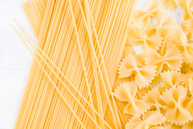 Dry raw pasta farfalle and spaghetti on the white background, natural light