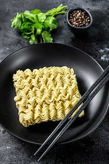 Dry, raw quick cooking noodle, instant noodles. black background. top view.