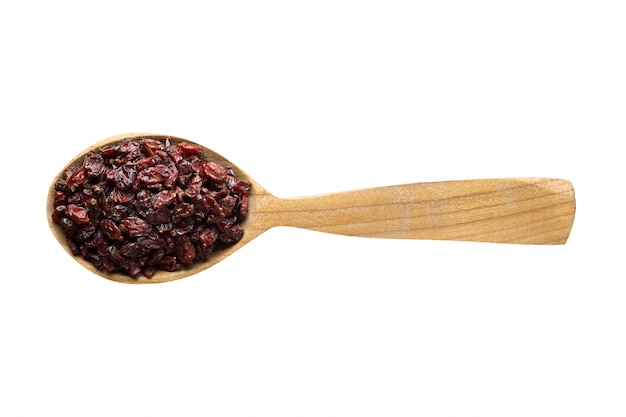 Dry red barberry for adding to food. spice in wooden spoon isolated on white.