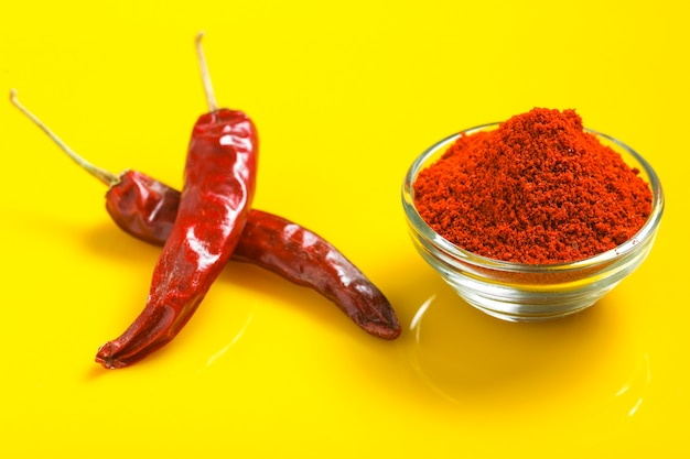 Dry red chilli with chilli powder in glass bowl on yellow surface