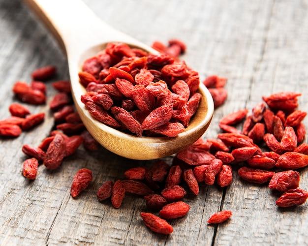 오래된 나무 표면에 건강한 식단을 위해 마른 붉은 구기 열매
