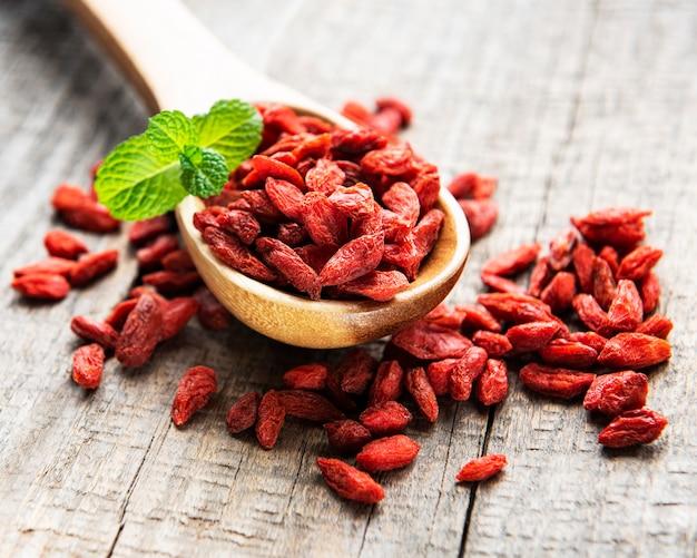 Сухие красные ягоды годжи для здорового питания на старой деревянной поверхности