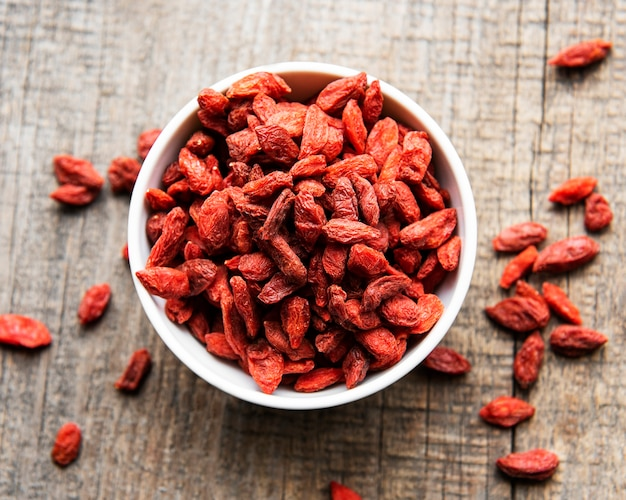 Dry red goji berries for a healthy diet on a old wooden background