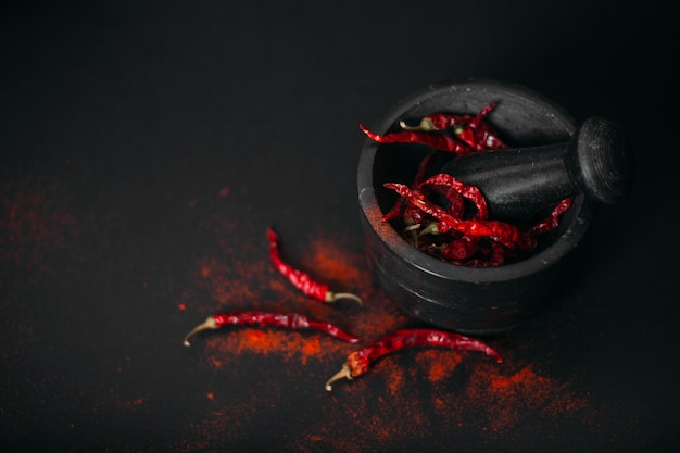 Dry red spicy peppers and powder in stone mortar on black.