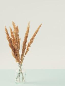 コピースペースのある木製のテーブルの上にモダンな花瓶で乾いた葦。耳からのドライフラワーの花束。