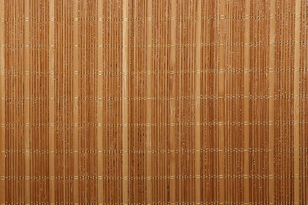 ドライリードの質感。黄色い杖の有機的な自然の壁紙。竹とわらと自然な暖かい木の背景