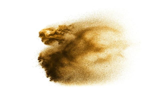 Сухой речной песок. золотой цветной песок всплеск на белом фоне.