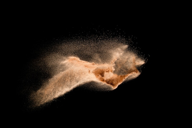Dry river sand explosion isolated on black background. abstract sand cloud.brown colored sand splash against dark background.