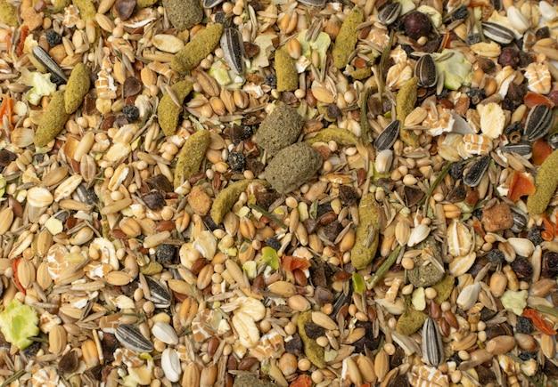 Сухой фон текстуры пищи грызунов для мыши, кролика или вид сверху дегу. сбалансированный режим кормления хомяка злаками, семенами, горохом, сушеными овощами