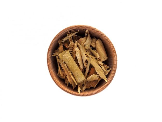 Сухая кора шиповника в деревянной чашке на белом столе