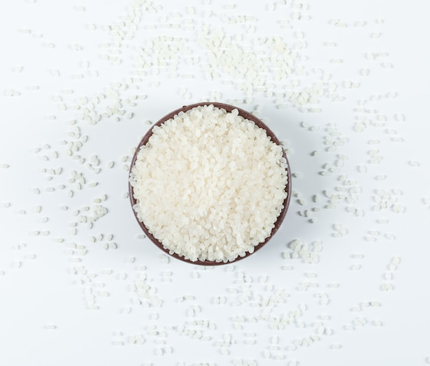 Dry round rice in a bowl top view on a white background