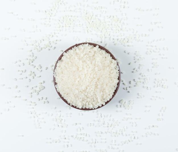 白い背景の上のボウルトップビューで丸い米を乾燥します。