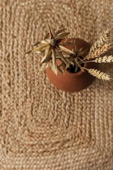 乾燥したライ麦、わらの上の赤い土鍋の小麦の茎