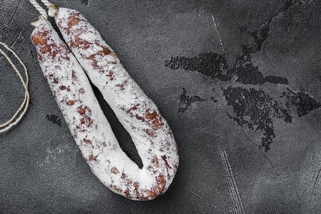 Сухая колбаса салями fuet на сером текстурированном фоне, плоская планировка с копией пространства.