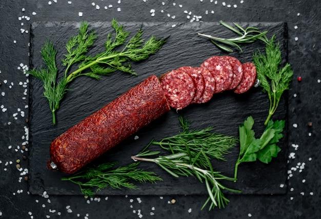 Сухая колбаса салями со свежим розмарином и специями на косточке