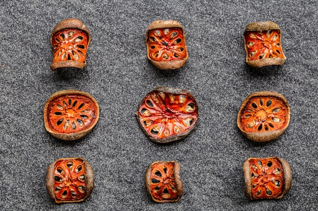 Dry slices of bael fruit (aegle marmelos) matum in wooden bowl on black background.