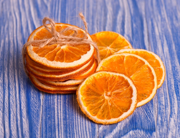 Dry slices of orange on blue vintage wooden table. aromatic spices. christmas decorations.