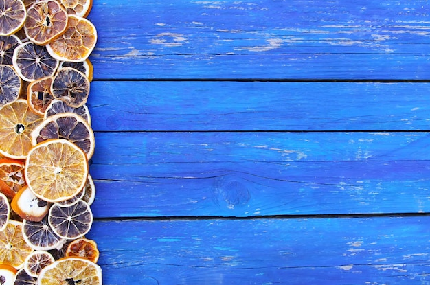 Dry slices of orange and grapefruit. fruit chips on aged blue wooden boards background.