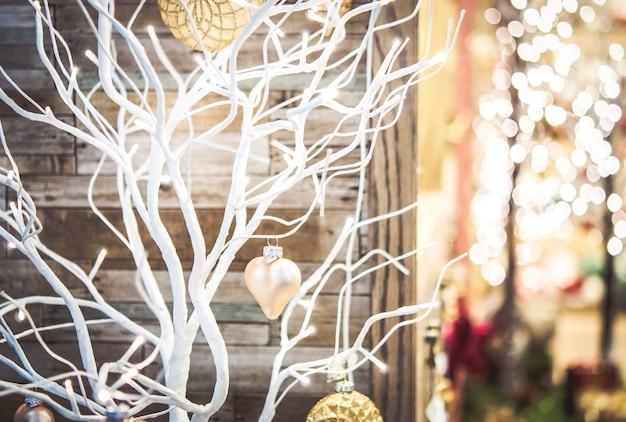 家の中の降雪のクローズアップ中に装飾的なおもちゃのハートで飾られた白い色で塗られた乾燥した小さな木。クリスマス冬新年風景の背景。コンセプト