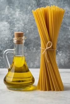 Сухие спагетти и бутылка оливкового масла на белом столе.