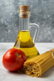 白いテーブルの上に乾いたスパゲッティ、オリーブオイルとトマトのボトル。
