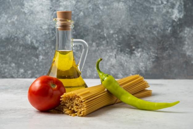 白いテーブルの上に乾いたスパゲッティ、オリーブオイルと野菜のボトル。