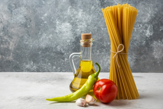 Dry spaghetti, bottle of olive oil and vegetables on white table.