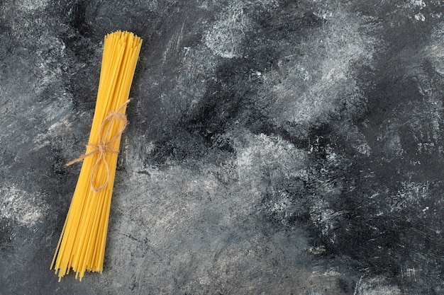 Spaghetti secchi legati con una corda sulla superficie di marmo