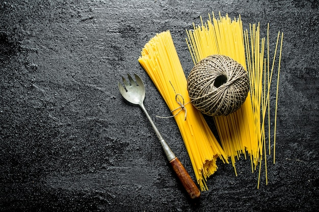 Dry spaghetti with twine and ladle. on black rustic background