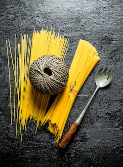 Dry spaghetti with twine and ladle. on black rustic surface