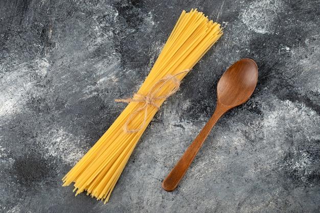 Spaghetti asciutti e cucchiaio di legno sulla superficie di marmo