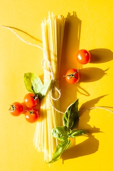 Dry spaghetti on a yellow background next to cherry tomatoes and a basil leaf