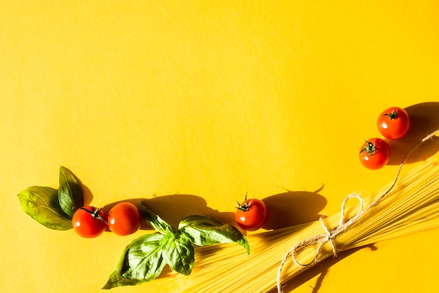 Dry spaghetti on a yellow background next to cherry tomatoes