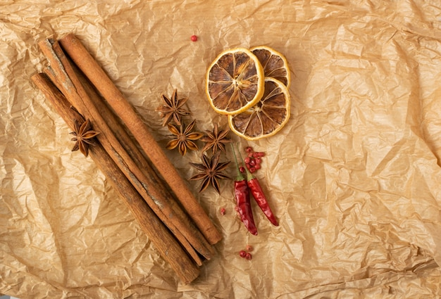 Dry spices for mulled wine with dehydrated sliced citrus on vintage kraft pack paper