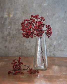 茶色の木製の背景、クローズアップショットのガラス瓶にナナカマドの乾燥小枝