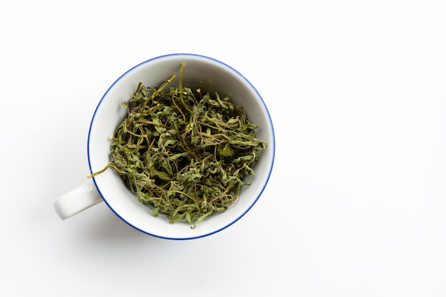 Dry stevia leaves in white cup on white surface