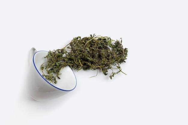白いカップで乾燥ステビアの葉