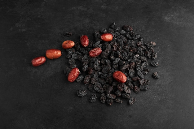 Dry sultanas and dates on black surface.